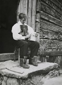 Elisabeth Meyer  A man in a Setesdal-costume on a stool in the doorway. He has a traditional container for milk products on his lap. Photographs from Setesdal around 1940-42. Gelatin silver print, baryta