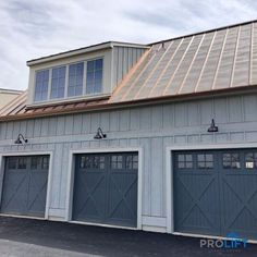 These carriage house garage doors fit-the-bill when it comes to style! Notice the X-brace panels combined with the vertical panel pattern as well as the top row windows with grilles. The unique color and gooseneck lighting are the perfect finishing touch for the overall design too. Nice job. | ProLift Garage Doors on Houzz | Project and Photo Credits: ProLift Garage Doors Haymarket, Va Red Garage Door, Faux Wood Garage Door, Carriage House Garage Doors, Garage Door Styles, Carriage Doors, Garage Door Design, Barn Doors, Outdoor Garage Lights, Garage Lighting