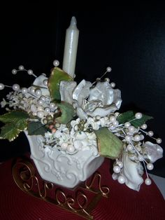 Pearls and Magnolias Holiday Floral Arrangement in Ceramic Sleigh. $25.00, via Etsy. A tastefully elegant one-of-a-kind piece! This ceramic sleigh has metal rails and has been lavishly and quite generously filled with a floral arrangement featuring large magnolias that have been individually painted with a pearlescent finish. Clusters of faux pearls and hydrangea blossoms accent the entire piece. The colors in the sleigh and candle are not quite ivory, but not bright white either.