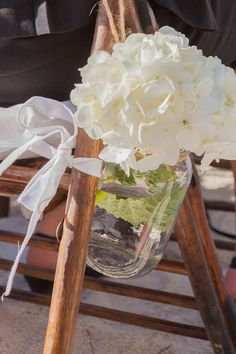 Mason jar flower arrangement with lace attached to a ceremony chair at Key Largo Lighthouse Beach Wedding Venue in the Florida Keys