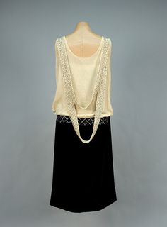 PANNE VELVET EVENING DRESS with RHINESTONES, 1920s. Bone silk sleeveless bodice having V-shaped band with diamond lattice of prong-set rhinestones and crystal beads terminating in black oval set in studded waistband of black skirt with cream center gore, back draped with two beaded swags.