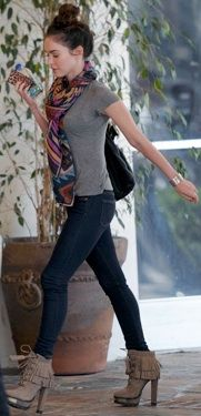 Megan Fox wearing skinny jeans, a gray tee shirt, a bold printed scarf and fringed lace-up ankle boots