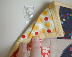 How to Hang a Mini Quilt by BECKY ...hanging a mini quilt with command hooks - learn how to use them.  Super simple and all you need is safety pins and command hooks.