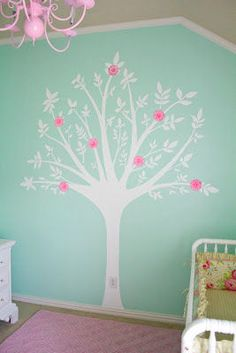 DIY painted tree baby nursery mural on an aqua blue wall in a baby girl room with pink flowers on the branches