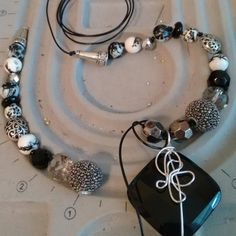 Stringing a long necklace with a large onyx pendant. Measure cord one and one-half times finished length to knot between beads.