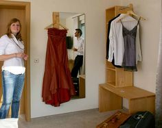 Am Psiegel lässt sich das lange Kleid aufhängen.  http://www.die-moebelmacher.de/produkte/wohnen/schlafzimmer/massivholzschlafzimmer14bis15.html