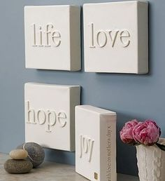 DIY – Canvas with wooden letters glued to it – then spray paint white – tada! Instant wall art! So easy!