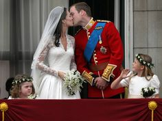 Prince William, Duke of Cambridge and Catherine, Duchess of Cambridge, kiss as Bridesmaids Grace Van Cutsem and Margarita Armstrong-Jones look on from the balcony at Buckingham Palace in London after the Royal wedding April 29, 2011. (Peter Macdiarmid/Getty Images