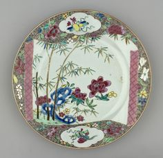 A Chinese famille rose porcelain plate, across the centre an unfurling scroll depicts bamboo & peony about a blue rock, outside of scroll of pink diaper pattern; upon grnd of brown spirals, shaped reserve above & below painted w emblems+