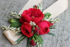 This ribbon tied wrist corsage features red piano garden roses, willow eucalyptus and pieris japonica