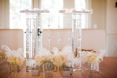 White, crystal and feather centerpieces | Photo: Scarlett & Stephen