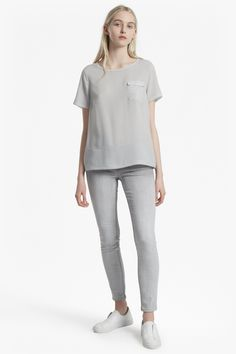 "<ul> <li> Short-sleeved woven-crepe top in t-shirt shape with raw edges</li> <li> Round neck</li> <li> Side pocket with flap</li> <li> Back button and rouleau loop fastening</li> <li> Loose fit — falls freely over the body</li> <li> UK size M length from high shoulder neck point is 65cm</li> </ul>  <strong>Our lead model is 5ft 10"" and is wearing a UK size M in Ros..."