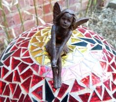 Photo of iron fairy atop red and gold glass mosaic sphere.