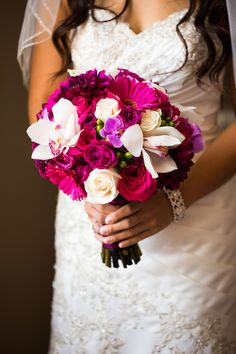 The bride carried a colorful bouquet composed primarily of white roses, white-and-fuchsia orchids, hot pink Gerber daisies, and pink roses. Photography: D. Park Photography. Read More: http://www.insideweddings.com/weddings/a-black-white-pink-wedding-in-august-inspired-by-cherry-blossoms/617/