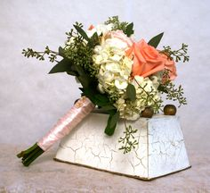 beautiful gardeny bouguet featuring coral roses , white hydrangea and seeded eucalyptus