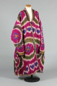 * Woven cotton/silk ikat khalat/coat, Uzbek first half 20th century, woven with watermelon roundels in deep magenta, blue and green with shot green silk lining, needlebraid borders
