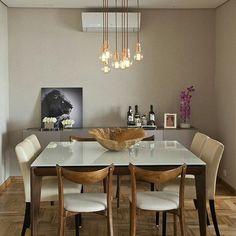 Sala de jantar com piso em taco, mesa com tampo branco e pés em madeira, cadeiras estofadas e buffet ao fundo.
