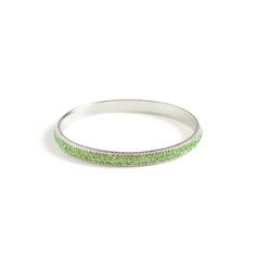 Claudette shimmers with peridot tones. This silver stunner will stack beautifully with silver bangles. www.themodernchicboutique.com