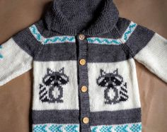 This custom made knitted sweater patterned with sly foxes is not only adorable but will keep your little one warm and cozy. It is sure to become both a practical and beautiful heirloom.  Perfect for a cool summer night,a brisk fall morning, or a snowy winters afternoon.  Message me with a size, colours, and personal details and I will work with you to create a truly unique sweater.  Sizes include: 12 months - chest size 21 inches 2 years - chest size 22 inches  3 years - chest size 23 inches…