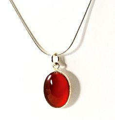 """CARNELIAN & SILVER PENDANT. A beautiful Carnelian Pendant hand crafted on Salt Spring Island by Alvero Sanchez.  The elegant Sterling Silver chain measures 18 inches. The carnelian stone measures 4/8 inch x 2/8 inch. Carnelian is said to help the wearer """"live in the moment"""" as well as restoring the natural energy flow of the body."""