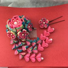濃いブルーの柄とピンクの生地で可愛らしく華やかな簪です。花のコーム簪の大きさは9㎝程、Uピンの下がりは12㎝程、Uピン小花簪3㎝程になります。