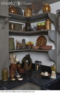 KITCHENS: period Colonial style kitchen storage detail, open shelves hold slipware pottery,