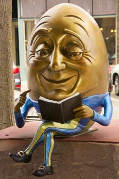 Kimber Fiebiger / 'Egghead' sculpture/statue of Humpty Dumpty sitting on wall reading a book, Sioux Falls SculptureWalk! Kewpie, Book Sculpture, Sculptures, Sioux Falls South Dakota, The Graveyard Book, Library Posters, Humpty Dumpty, Kid Character, Egg Art
