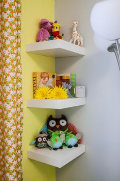 Cute shelves and toys adorn a yellow accent wall. #nursery #owls