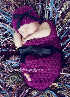 baby with hat in crocheted cocoon