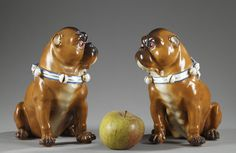 A pair of ochre, brown and white porcelain dogs wearing a necklace decorated with ribbon and small spherical bells. Anti-skid skates in lightweight felt. French work, 19th century...