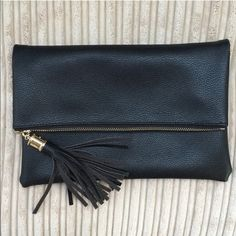 Black clutches with tassel Beautiful black clutch tassel with gold chain.  It has interior slot pocket and zipper pocket.  It's perfect for night out!  It measures 10.50in x 7in.  PU leather. Bags Clutches & Wristlets