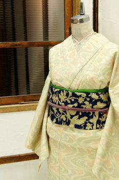 クリーム色の地に、赤や緑や紺青の色糸が優しく映え、流水のような霞のようなゆらぎのある曲線模様が織り出された正絹紬の単着物です。