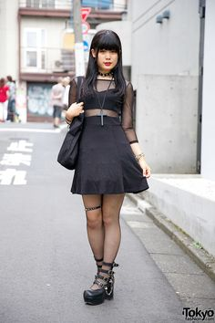 18-year-old Yuka on the street in Harajuku wearing a black dress with sheer panels, fishnets, strappy Yosuke heels, a Hellcatpunks cross necklace, and a Ghost of Harlem cross ring.
