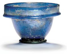 A ROMAN BLUE GLASS PATELLA CUP  1ST CENTURY A.D.  The body with gently flaring sides, the short vertical rim emerging from a folded flanged collar, on pad foot, with iridescence  2¾ in. (7 cm.) diam.