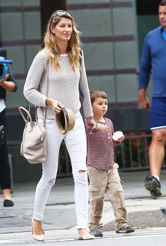 Gisele Bundchen shows off her simple style  in a knit sweater, Rag & Bone Jeans, and baby powder cross-body.