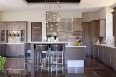 William Ohs cabinetry in quarter-sawn oak with a gray washed finish and glaze lines the perimeter of this contemporary kitchen. A Terzani crystal droplet chandelier highlights the L-shaped Silestone island. A Phillip Jeffries grass cloth adds depth to the Contemporary Kitchen Renovation, White Contemporary Kitchen, Transitional Kitchen, Neutral Kitchen, Kitchen White, Country Kitchen, New Kitchen, Kitchen Decor, Kitchen Ideas