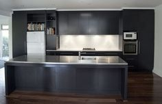 One of the things that we love most about this kitchen is the space above the fridge is open shelving. It sports dark satin finished 2 pack doors, a stainless steel bench top on the island bench and a cesarstone bench top on the cook top bench, and a beautiful arrangement of small white tiles. What do you think?  www.davisandparkkitchens.com.au/renovation-service.html