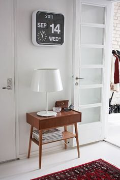 Karlsson Flip Clock above a mid century table with simple white lamp. Contemporary look.