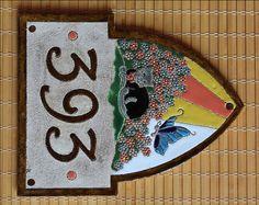 Domovní číslo z keramiky - kočka s motýlkem v květinové zahradě. Výroba keramiky na zakázku. Keramika pro domov, www.keramika-dum.cz. House number