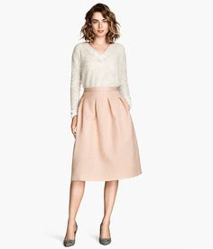 Knee-length, gently flared skirt in fabric with a woven pattern, heavy drape, and crinkled surface. Pleats at front and back and concealed back zip