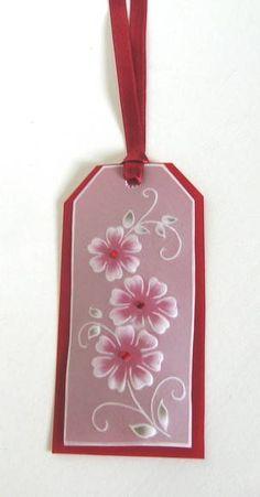 Marcador em papel vegetal, com desenhos em relevo, fita de cetim e detalhes em cristais. Pode conter mensagem na parte posterior. Dimensões aproximadas: 11x5,5 cm. Pedido mínimo: 20 unidades. R$ 3,00