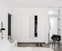 entire wall of built-in closet, wardrobe, or storage. prefer mirror doors and extending the storage cubbies over the door to the bedroom. light and white small bedroom.