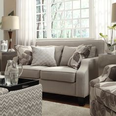 Give your home decor a comfortable finishing touch with this densely padded Ellyson loveseat. Upholstered in a neutral, light grey fabric to match a variety of settings, this elegant chair features track arms and tapered espresso-stained legs.