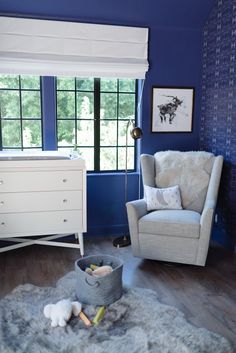 A little boy's Star Wars themed blue nursery with gray rocking chair and sheepskin throws