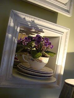 A grouping of African violets, in tea cup, in shadow box.
