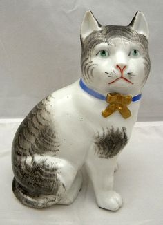 """Japanese Meiji Period (1868-1912) KUTANI Porcelain Okimono of a seated Cat with a collar. The cat has life-like decorations over its head and back, light-green enamel eyes, light -blue collar with gold, a bow and red enameling over its mouth. The Okimono is in excellent condition with no damages and no losses. 7 3/4"""" tall x 5 1/2"""" long x 4"""" deep. Blue Dinning Room, Staffordshire Dog, Japanese Porcelain, Laurel Burch, Asian, Vintage Cat, Cat Art, Cats And Kittens, Kitty"""