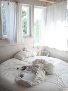 white & cozy, yum i want a round bed or what a great reading area!