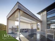 Lounge tuin onder geïntegreerd lamellendak. Buitenkeuken onder terrasoverkapping met lamellen.