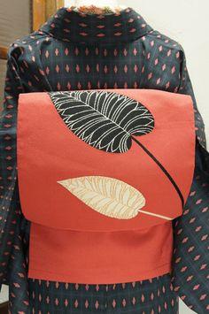 オレンジとベージュとピンクをとけあわせたようなスモークがかった珊瑚色の地に、銀の葉脈美しい黒の葉と、金の葉脈美しい白の葉のモチーフが凛と織り出されたモダンでアートな開き名古屋帯です。