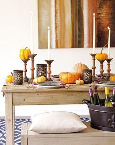 Zierkürbisse auf Kerzenständern und schöne Tischdeko